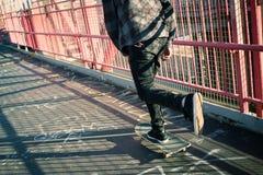 Skateboarder cruise on bridge Stock Image