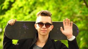 Skateboarder dell'adolescente del metraggio che tiene un pattino e che esamina la macchina fotografica 4K video d archivio