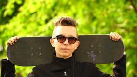 Skateboarder dell'adolescente del metraggio che tiene un pattino e che esamina la macchina fotografica 4K archivi video