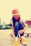 Skateboarder della giovane donna che lega laccetto Fotografie Stock