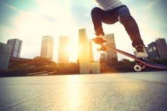 Skateboarder die bij zonsopgangstad met een skateboard rijden royalty-vrije stock afbeeldingen