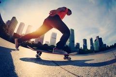 Skateboarder die bij zonsopgangstad met een skateboard rijden stock foto