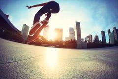 Skateboarder die bij zonsopgangstad met een skateboard rijden stock foto's