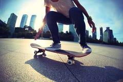 Skateboarder die bij zonsopgangstad met een skateboard rijden royalty-vrije stock afbeelding