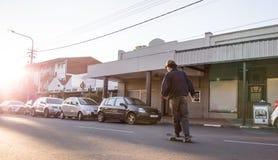 Skateboarder die onderaan weg in de stad schaatsen royalty-vrije stock foto's
