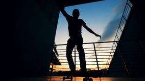Skateboarder die op een zonsondergangachtergrond springen, langzame motie stock videobeelden