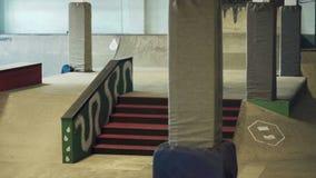 Skateboarder die truc op de sporen in skatepark doen stock videobeelden
