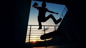 Skateboarder die trucs op een zonsondergangachtergrond doen in langzame motie stock video