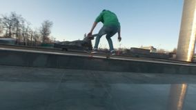 Skateboarder does extreme tricks on the ramp outdoors in sunset stock footage