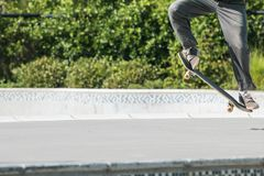 Skateboarder Does Trick Out Of Bowl At Skateboard Park. A skateboarder uses his legs and feet to execute a skateboard trick at a skateboard park Stock Image