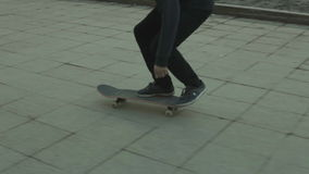 Skateboarder does a trick outdoors stock footage