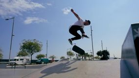Skateboarder does a trick outdoors. Young male skateboarder does a trick outdoors stock video