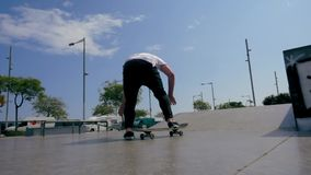 Skateboarder does a trick outdoors stock video footage