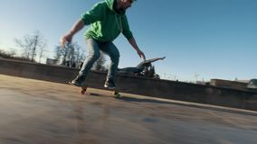 Skateboarder does tricks jumping on the ramp outdoors stock footage