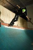 Skateboarder doing backside smith grind on ramp Stock Photography
