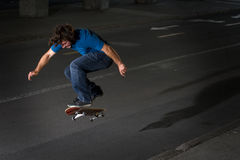 Skateboarder doing a flip on street Royalty Free Stock Photography