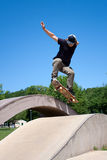 Skateboarder Doing a Jump at. Action shot of a skateboarder performing a jump at a skate park Royalty Free Stock Photography