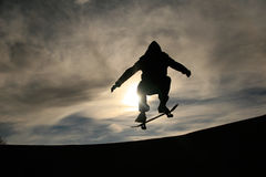 Skateboarder doing ollie in sunset Stock Photo