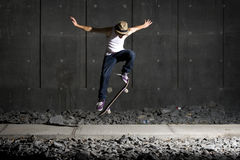 Skateboarder doing an ollie on walking path Stock Image