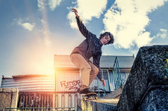 Skateboarder doing a skateboard jumping trick at sunrise city Royalty Free Stock Photography
