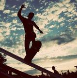 Skateboarder doing a slide trick. Skateboarder silhouette doing a slide trick Royalty Free Stock Image