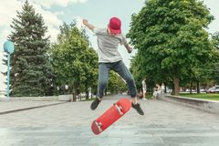 Skateboarder doing a trick at the city`s street in sunny day. Young man in sneakers and cap riding and longboarding on the asphalt. Concept of leisure activity royalty free stock photography