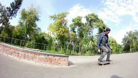 Skateboarder doing trick on grindbox in the skate park banque de vidéos