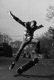 Skateboarder Doing Tricks. A skateboarder performing jumps or ollies on asphalt.  Slight motion blur showing the movemant on the arms and legs Stock Image