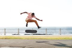Skateboarder doing tricks and jumping on the road by the beach. Full length portrait of a young skateboarder doing tricks and jumping on the road by the beach Stock Photos