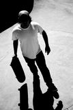Skateboarder Dude Silhouette. Silhouette of a skateboarder standing inside the pool at the skate park with strong contrast and dramatic shadows. Black and white Royalty Free Stock Photos