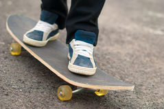Skateboarder feet in sneakers on a skateboard. Royalty Free Stock Photography
