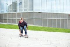 Skateboarder giù la collina nella via. Fotografia Stock