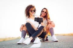 Skateboarder girl taking self portrait on smartphone. Skateboarder girl taking self portrait Royalty Free Stock Photos