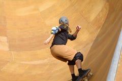 Skateboarder going. Skateboarder riding the bowl stock images