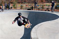 Skateboarder Grabs Board Doing Trick In Big Bowl Stock Photos