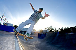 Skateboarder on a grind. At sunset at the local skatepark Stock Images