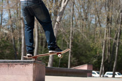 Skateboarder on a Grind Rail. Action shot of a skateboarder skating at the park on a concrete rail Stock Photography