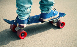 Skateboarder in gumshoes standing on his skate Royalty Free Stock Image