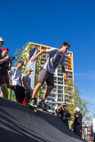 Skateboarder in the halfpipe takes the trick. Skateboarder with friends in skatepark jumping in the halfpipe. The opening of the center of extreme sports for Stock Photography