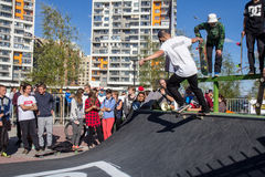 Skateboarder in the halfpipe takes the trick. Skateboarder with friends in skatepark jumping in the halfpipe. The opening of the center of extreme sports for Royalty Free Stock Photo