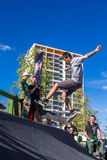 Skateboarder in the halfpipe takes the trick. Skateboarder with friends in skatepark jumping in the halfpipe. The opening of the center of extreme sports for Royalty Free Stock Image