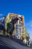 Skateboarder in the halfpipe takes the trick. Skateboarder with friends in skatepark jumping in the halfpipe. The opening of the center of extreme sports for Stock Image
