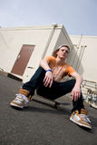 Skateboarder Hanging Out. A young skater resting on his skateboard Royalty Free Stock Photography