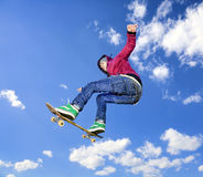 Skateboarder high in air. Skateboarder jumps high in air on background the blue sky with clouds Royalty Free Stock Photo