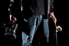 Skateboarder Holding a video camera and a skateboard. Isolated on black background Stock Photo