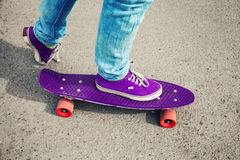 Skateboarder in jeans, feet fragment with skate Royalty Free Stock Images