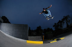 Skateboarder jumping from ledge. Extreme sports / skateboarder jumping off a ledge stock photography