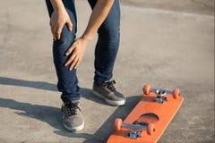 Skateboarder kreeg sprintenverwonding het met een skateboard rijden Stock Fotografie