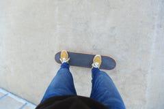Skateboarder legs riding skateboard at city skatepark Stock Photo