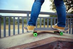 Skateboarder legs riding skateboard at city skatepark Stock Photos